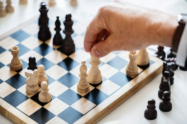 Black and white chessboard with a hand moving a piece.