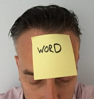 Post it note with word written on it on a man's head