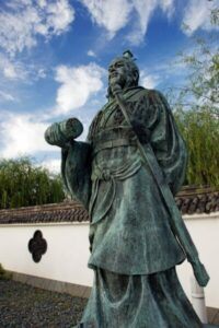 A monument of strategist Sun Tzu outdoors against white wall