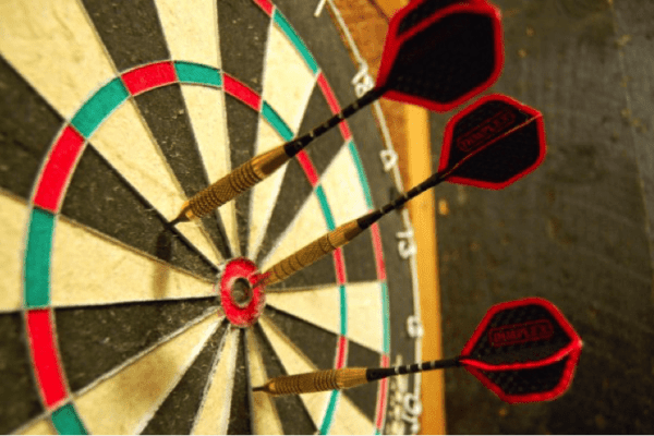 Dartboard with three darts in the centre