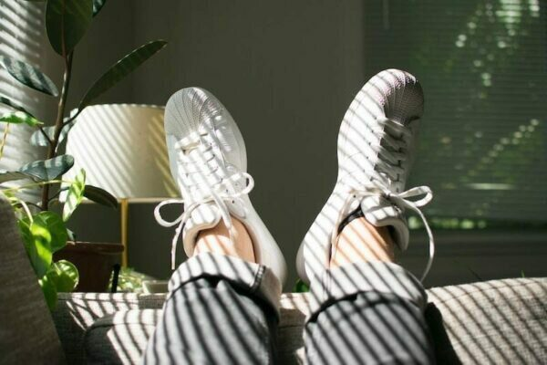 Feet resting on the end of a sofa