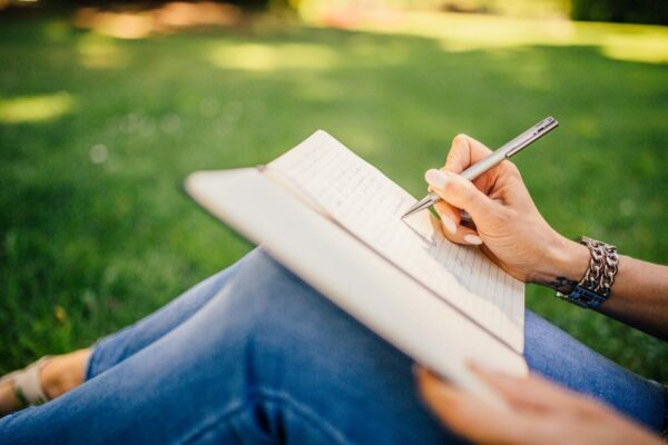 Woman writing in notebook on grass
