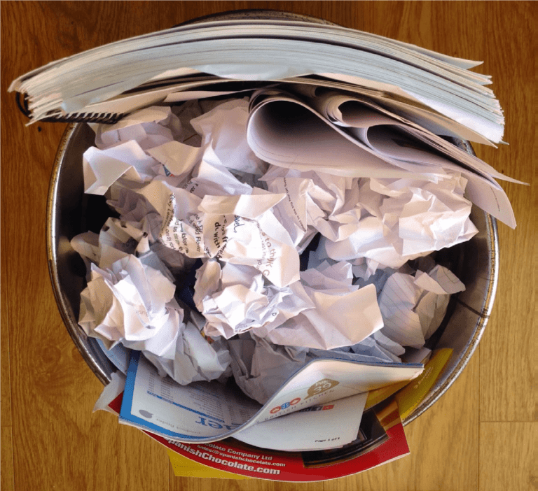A metal bin full of waste paper and a notebook