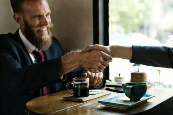 A businessman shaking the hand of a man over coffee at a cafe