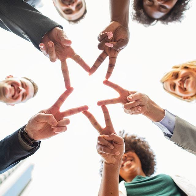 5 people of varying backgrounds holding their fingers out to form a star