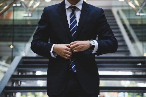 Man in business attire buttoning his coat