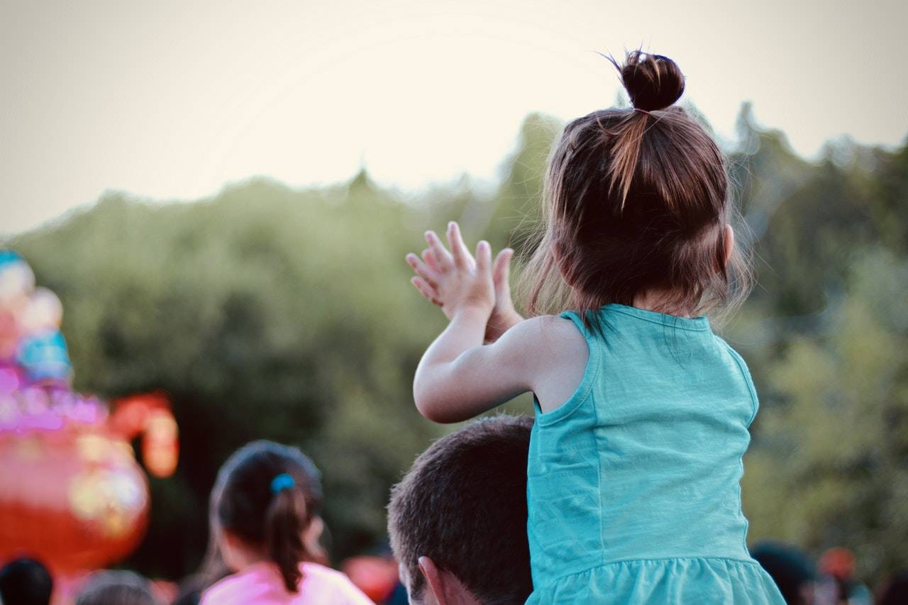 Child on man's shoulders, clapping