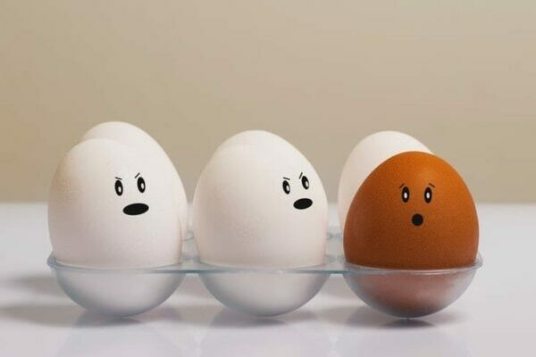 A tray of white eggs with faces and a singular brown egg