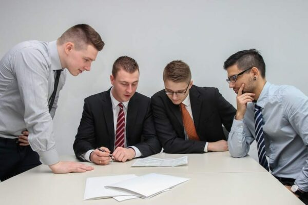 Four businessmen gathered around a table looking at paperwork