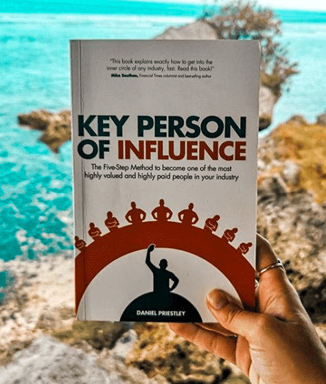 Hand holding book Key Person of Influence by Daniel Priestly in front of a seashore