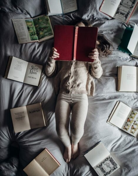 Little girl reading a red book while lying down on a soft bed with opened books surrounding her