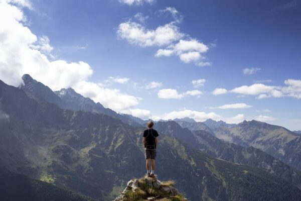 Man on the edge of a cliff. looking at the view of a mountain landscape