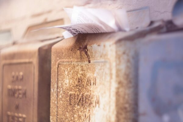 Concrete postbox overflowing with papers