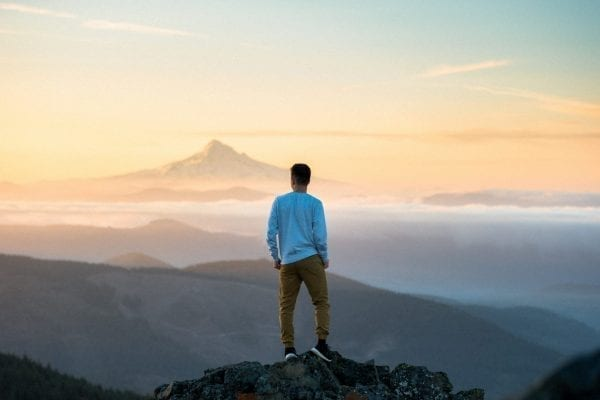 Man stood on top of a mountain looking out at the horizon
