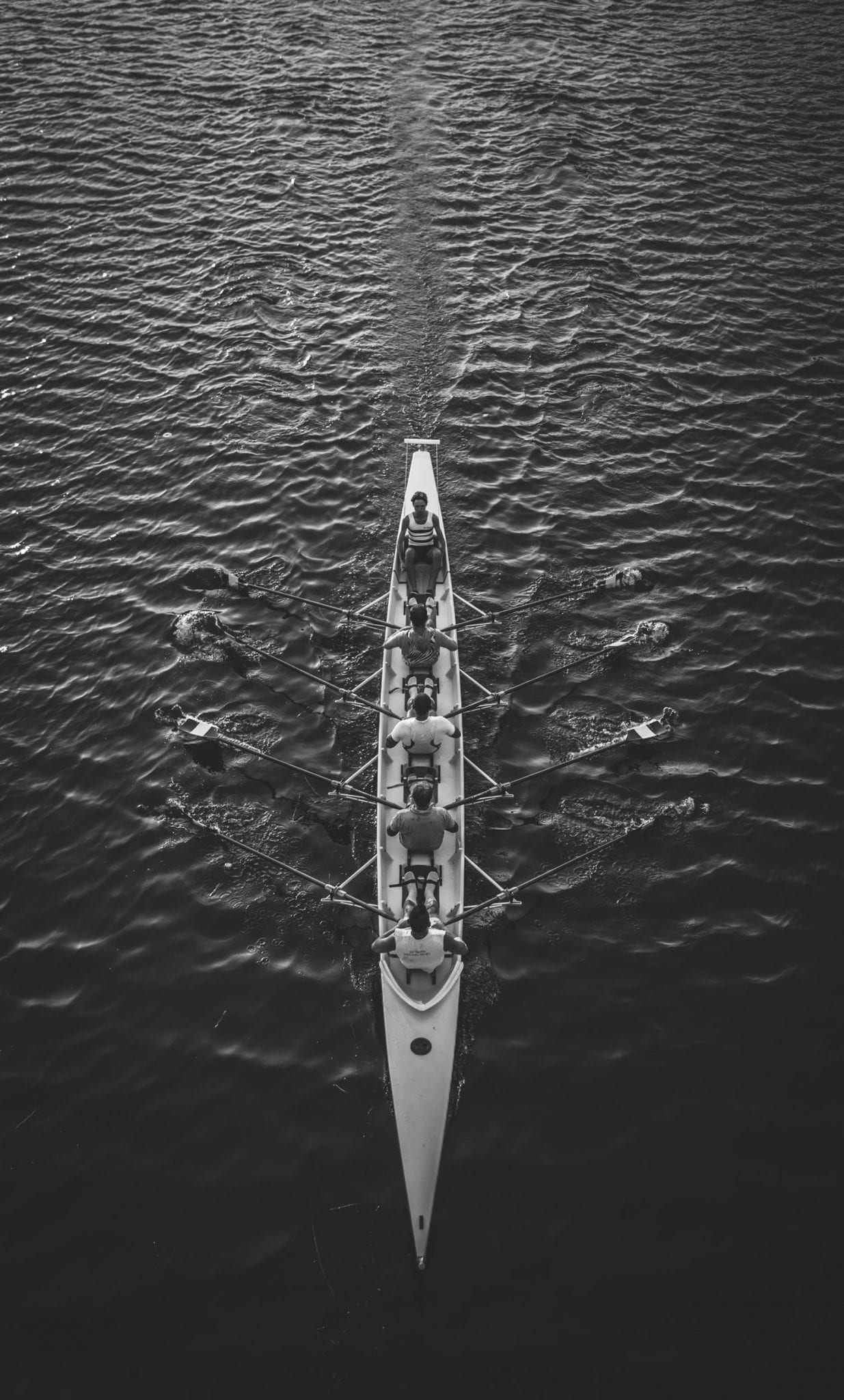 Top view of a rowing team in a rowboat in the middle of the sea