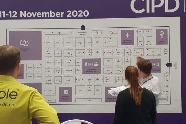 3 business people looking at a CIPD chart on the wall