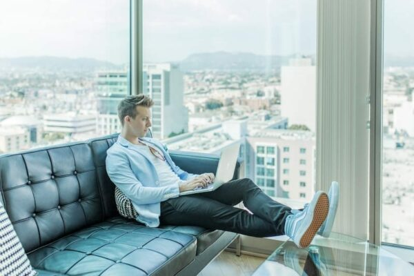 Man using his laptop while sitting on a black sofa beside the windows of a tall building