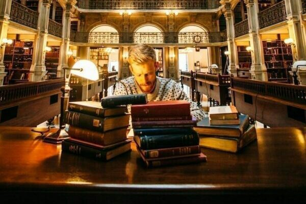 Man working in a library with books in front of him