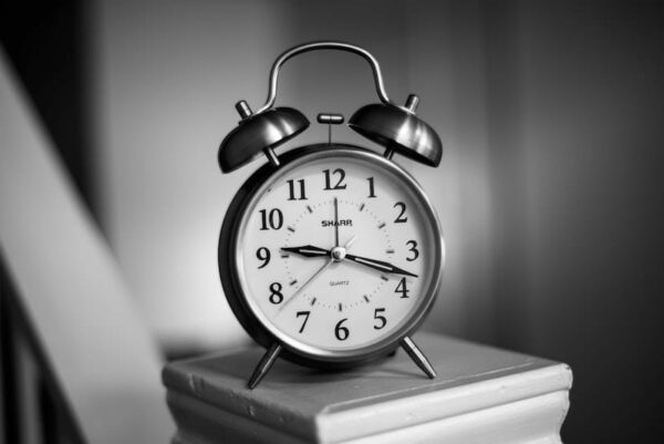 A black and white picture of a vintage alarm clock, on a bedside cabinet.