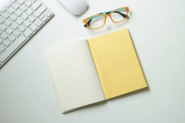 A yellow, blank not book lay out on a white desk. Accompanying the notebook is a pair of orange spectacles set out neatly.