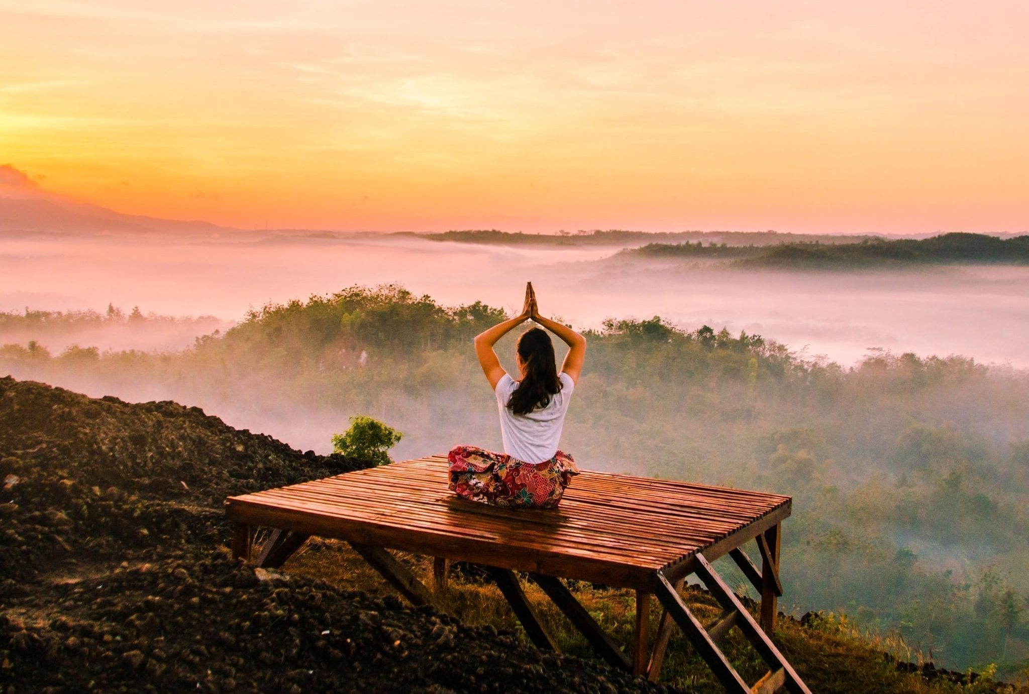 Girl on a wooden bed while meditating in front of a beautiful scenery