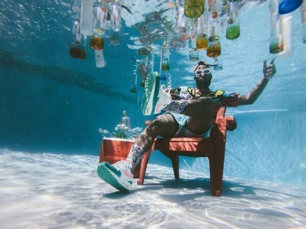 Man in party attire sitting on a chair underneath the pool with alcohol bottles