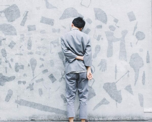 Man facing the wall with his left hand holding his right arm