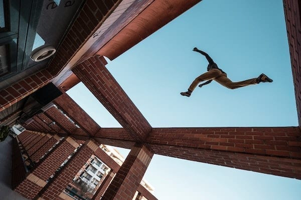 Person doing parkour around buildings