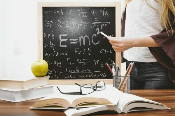 Woman in front of chalk board with E=mc2 on it