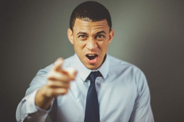 Man in business attire pointing at you