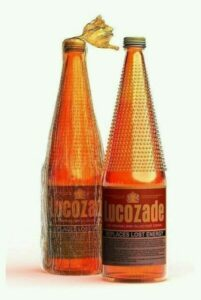 Two bottles of Lucozade with the gold foil top,