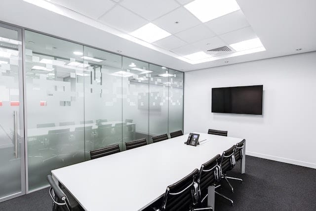 A black and white empty boardroom with chair and a screen.