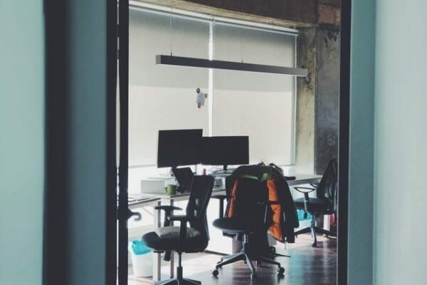 An empty office space with empty desks and computers