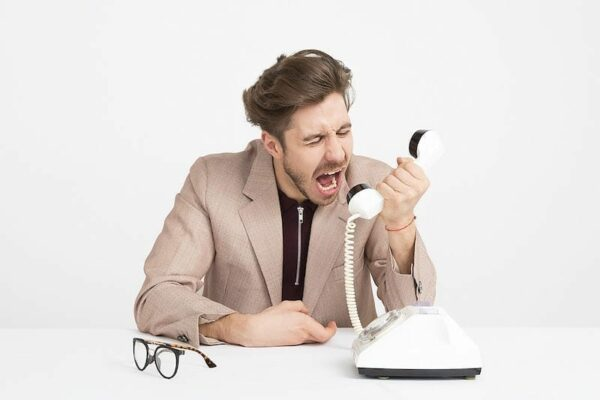 Businessman sat at table shouting into a telephone