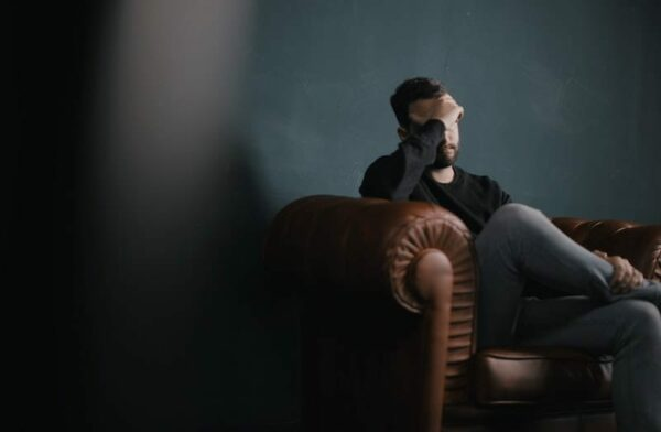 Man sitting on a chair with his hand touching his forehead as if he's worried