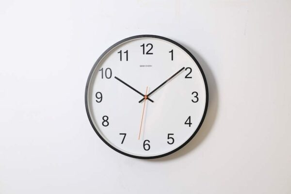 Clock mounted on a white wall with time showing 10:10