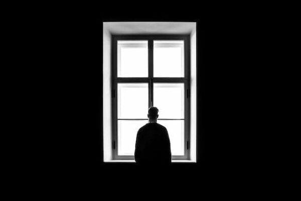 Silhouette of a man looking out of a window