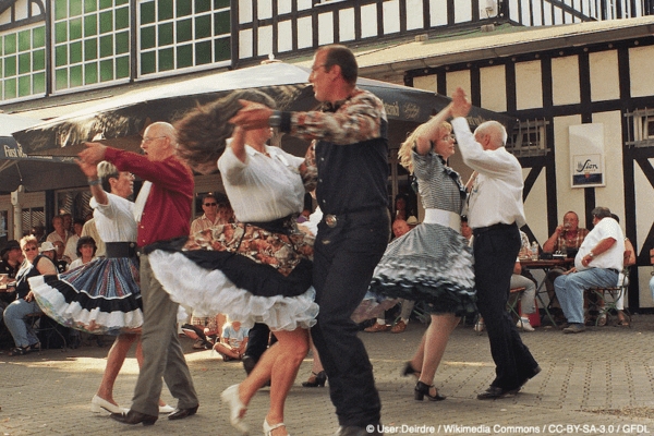 A group of people dancing in pairs outside a pub
