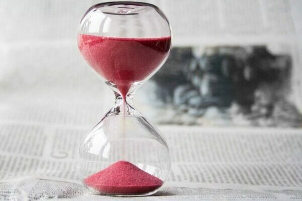 Clear sand timer with red sand in it