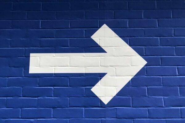 White arrow on blue background
