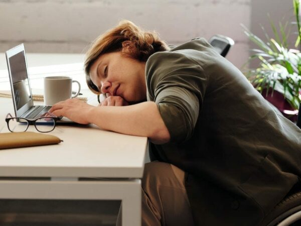 exhausted lady sleeping beside a laptop,