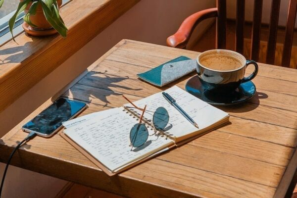 sunglasses and a pen on top of a journal on a coffee table.