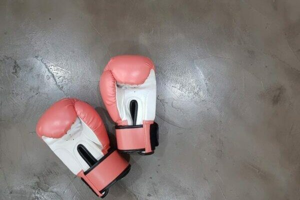 A pair of pink boxing gloves on the floor