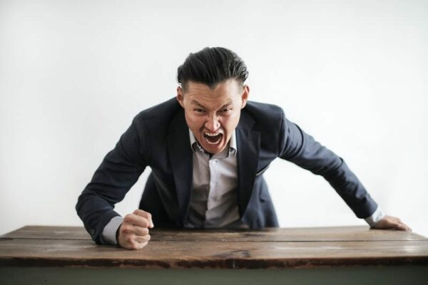 Angry man banging his fist on wooden table