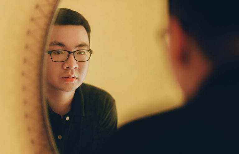 Man with glasses looking in the mirror at himself