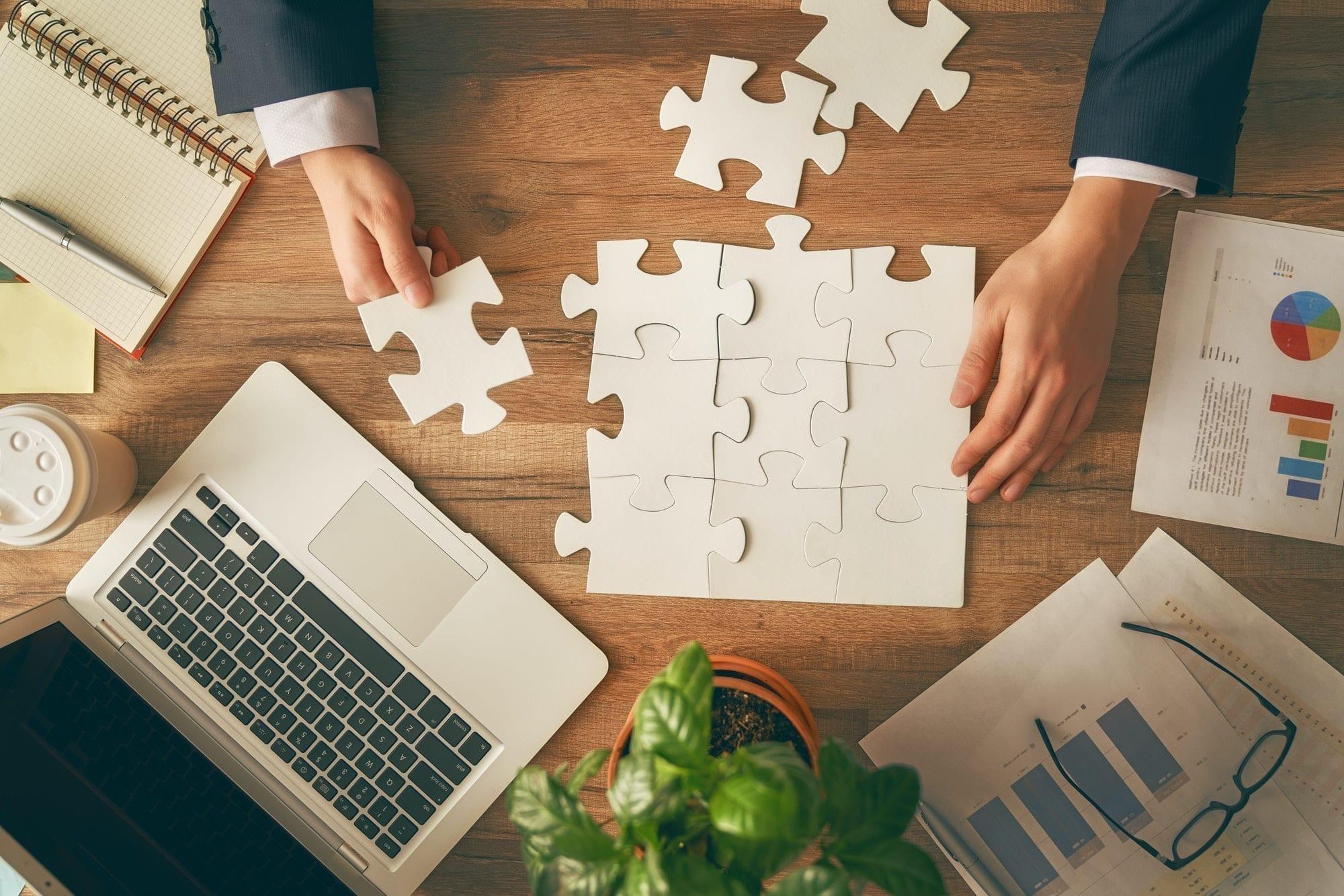 Businessman's hands putting together a paper jigsaw