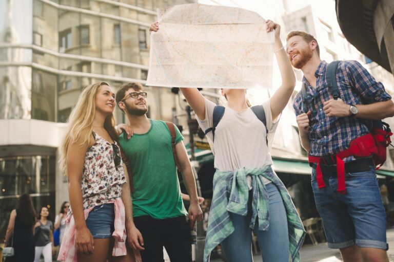 Group of three being led by a tour guide looking at a map in a city