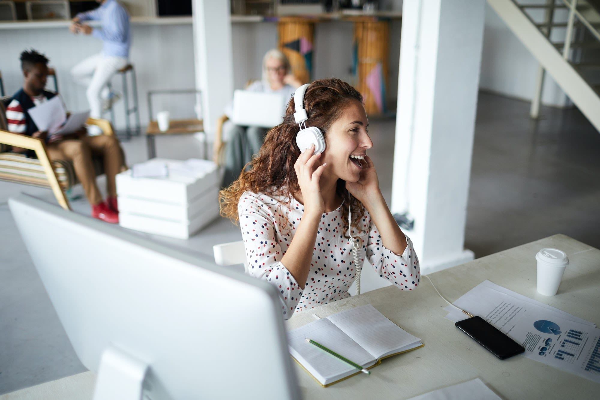 Woman with headphones on at work laughing