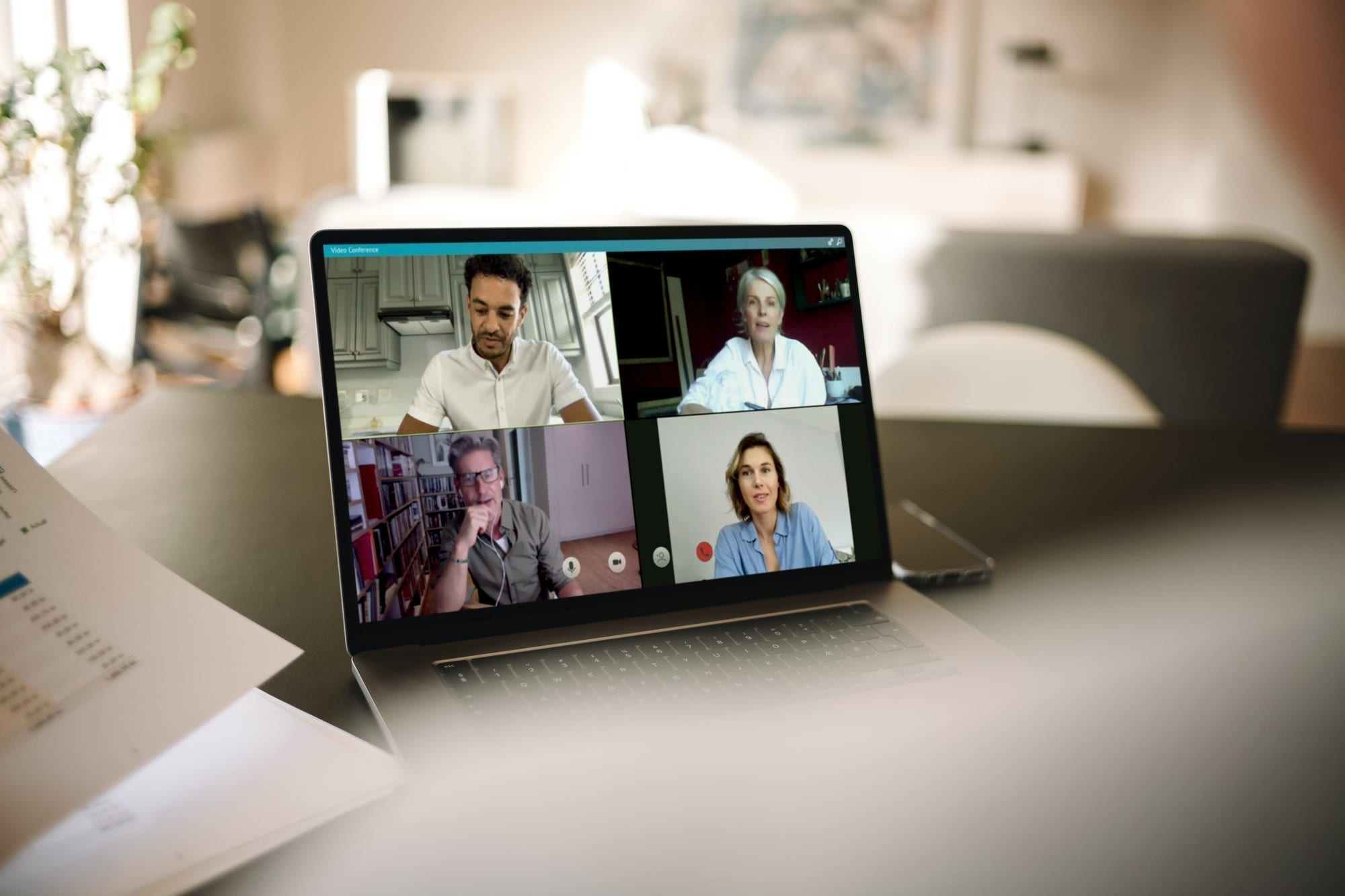 A four-way video call on a laptop at home