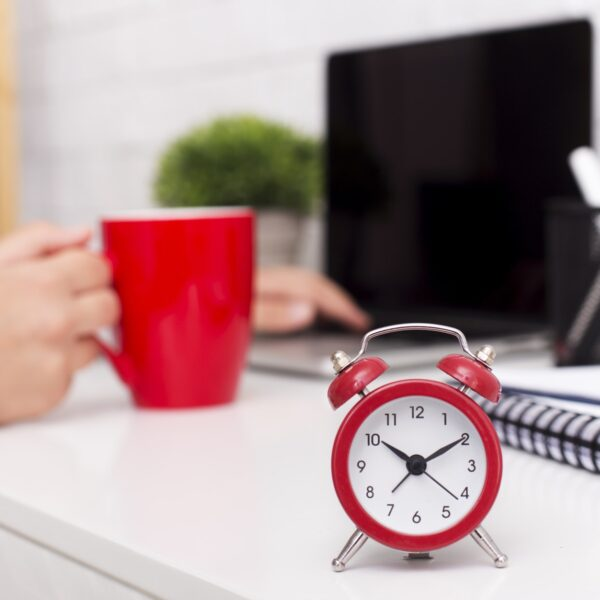 Red alarm clock and morning cup of coffee on office table, time management techniques